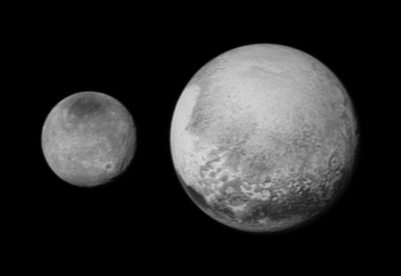 """Pluto (right) and largest moon Charon compared to scale in a composite of separate images taken by New Horizons on 12 July from a distance of 1.6 million miles (2.5 million kilometres). Pluto's bright, mysterious """"heart"""" is rotating into view, the target of the highest-resolution images that will be taken during the spacecraft's closest approach to Pluto on 14 July. The intriguing """"bulls-eye"""" feature at right is rotating out of view, and will not be seen in greater detail. Charon's newly-discovered system of chasms, larger than the Grand Canyon on Earth, rotates out of view in New Horizons' sharpest image yet of the Texas-sized moon. It's trailed by a large equatorial impact crater that is ringed by bright rays of ejected material. In this latest image, the dark north polar region is displaying new and intriguing patterns. Image credits: NASA/JHUAPL/SWRI."""