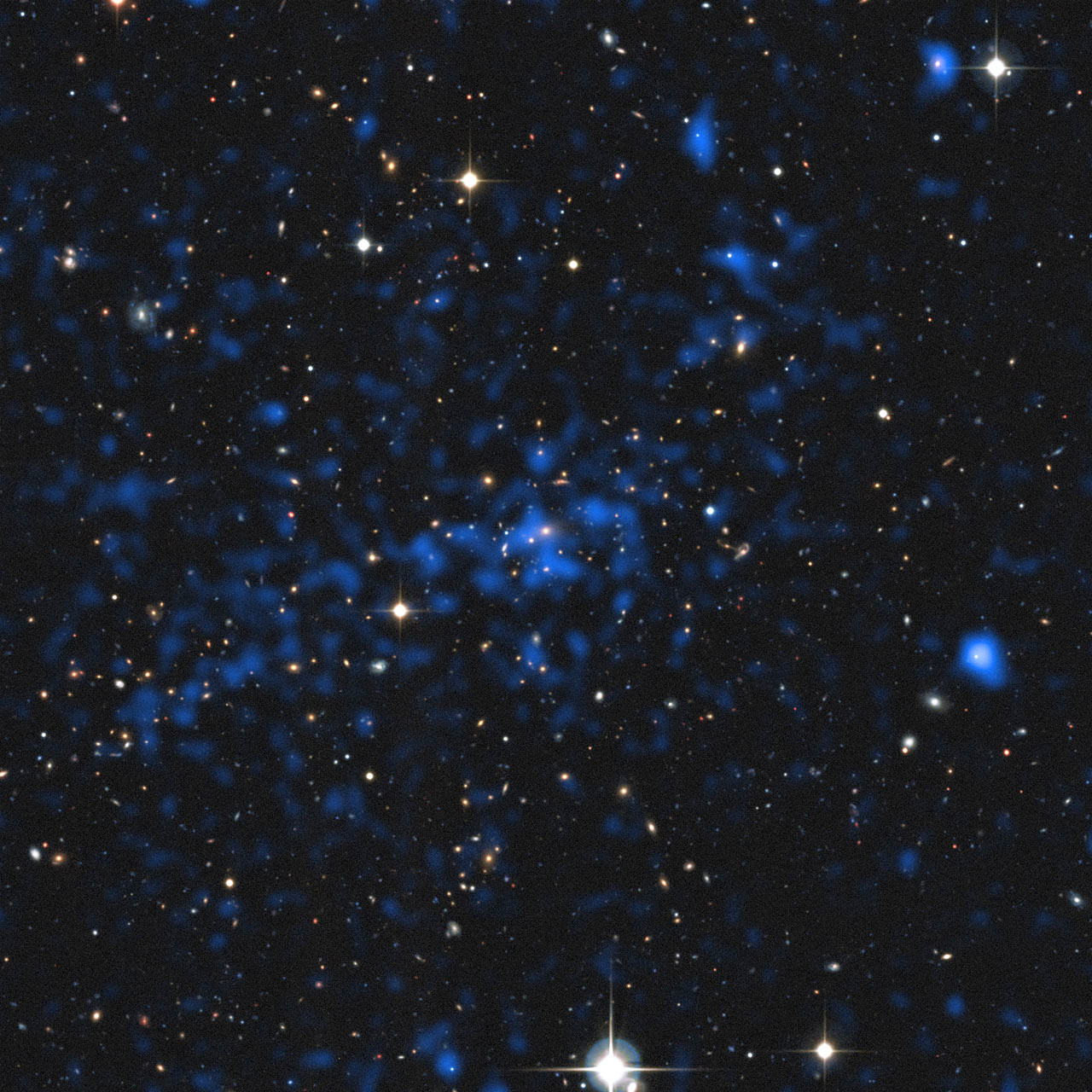 This image superimposes an X-ray image of a distant cluster (the blue image, from ESA's XMM-Newton satellite) on top of a ground-based view of the sky (from the Canada France Hawaii Telescope). Some of the brightest X-ray objects are galaxies with brilliant centres powered by supermassive black holes. The cluster at the centre of the picture shows up as an extended patch of X-ray emission, coming from hot gas. Image credit: ESA/XXL consortium/Canada France Hawaii Telescope.
