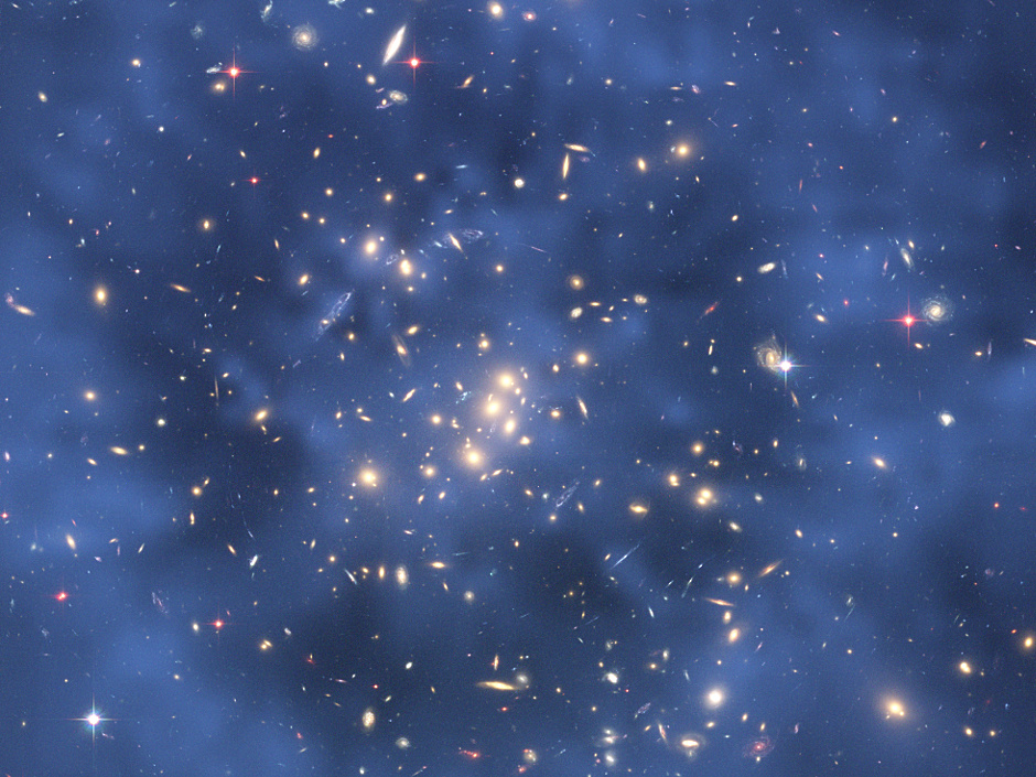 This Hubble composite image shows the ring of dark matter in the galaxy cluster CL 0024+17. The ring-like structure is evident in the blue map of the cluster's dark matter distribution. The map was derived from Hubble observations of how the gravity of the cluster CL 0024+17 distorts the light of more distant galaxies, an optical illusion called gravitational lensing. Although astronomers cannot see dark matter, they can infer its existence by mapping the distorted shapes of the background galaxies. Image credit: NASA, ESA, M.J. Jee and H. Ford (Johns Hopkins University).