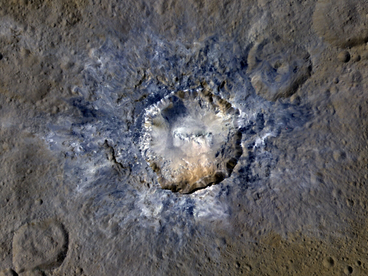 Ceres' Haulani Crater, with a diameter of 21 miles (34 kilometres), shows evidence of landslides from its crater rim and rays of bluish ejected material in this enhanced false-colour view. Image credit: NASA/JPL-Caltech/UCLA/MPS/DLR/IDA.