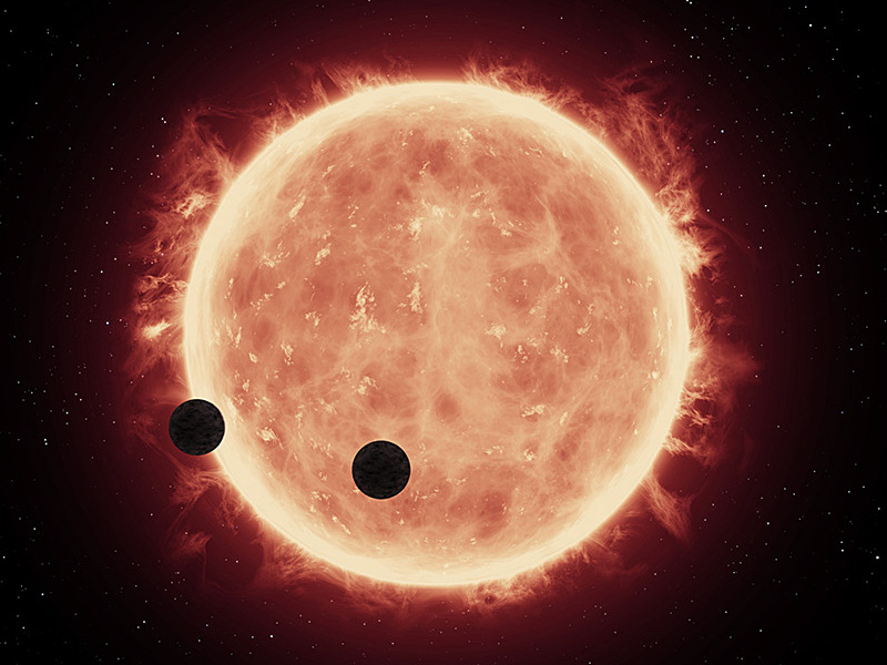 This illustration shows two Earth-sized worlds passing in front of their parent red dwarf star, which is much smaller and cooler than our Sun. The planets, TRAPPIST-1b and TRAPPIST-1c, reside 40 light-years away. They are between 20 and 100 times closer to their star than Earth is to the sun. Researchers think that at least one of the planets, and possibly both, may be within the star's habitable zone, where moderate temperatures could allow for liquid water on the surface. Hubble looked for evidence of extended atmospheres around both planets and didn't find anything. This leaves open the possibility the planets have thinner, denser atmospheres like Earth's. Illustration credit: NASA, ESA, and G. Bacon (STScI). Science credit: NASA, ESA, and J. de Wit (MIT).