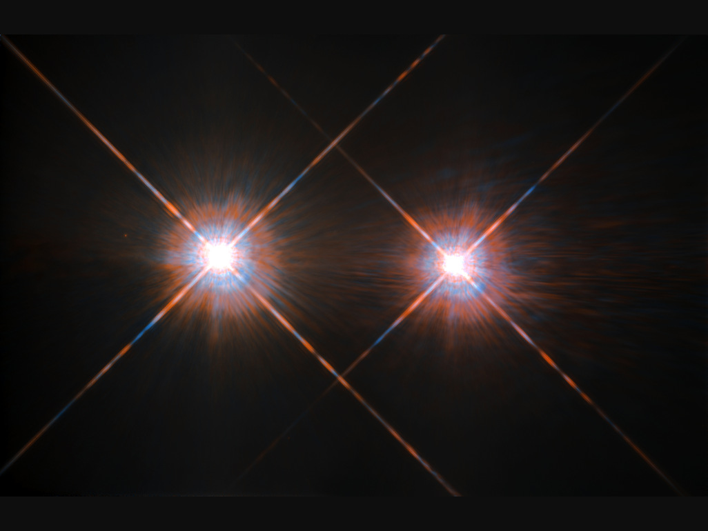 This NASA/ESA Hubble Space Telescope portrait of AlphaCentauri was produced by observations carried out at optical and near-infrared wavelengths. The cruciform spikes around each star are due to diffraction effects within the telescope's optical system. Compared to the Sun, AlphaCentauriA (left) is of the same stellar type G2, and slightly bigger, while AlphaCentauriB (right), a K1-type star, is slightly smaller. They orbit a common centre of gravity once every 80 years, with a minimum distance of about 11 times the distance between the Earth and the Sun. The AlphaCentauri group is completed by a faint red dwarf, ProximaCentauri (not shown), recently revealed to possess an Earth-like planet orbiting in its habitable zone. Image credit: ESA/Hubble & NASA.