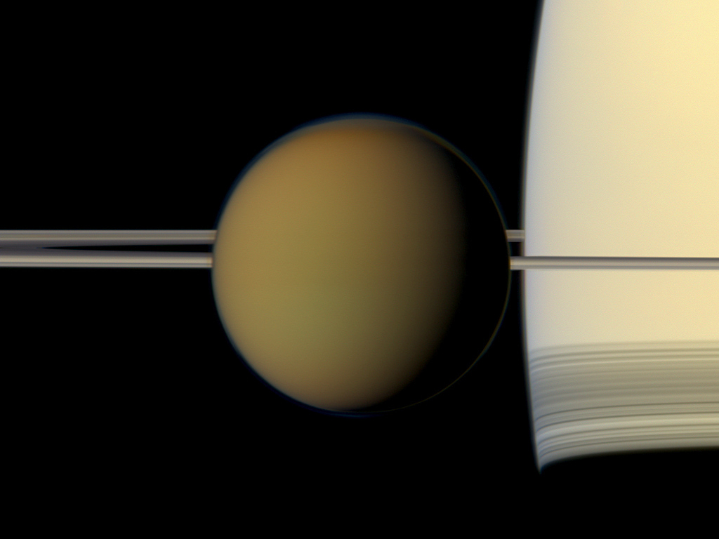 The hazy globe of 3,200-mile-wide Titan hangs in front of parent planet Saturn and its rings in this natural colour view from NASA's Cassini spacecraft. Image credit: NASA/JPL-Caltech/Space Science Institute.